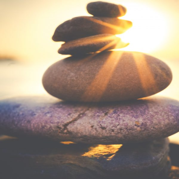 stones balanced on top of one another with the sun shining behind, representing peace and relaxation