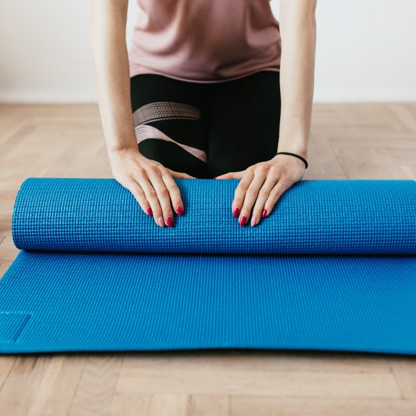 rolling out a mat in a pilates class